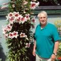 Geraldine's husband, Gerald, standing next to her tree lillies